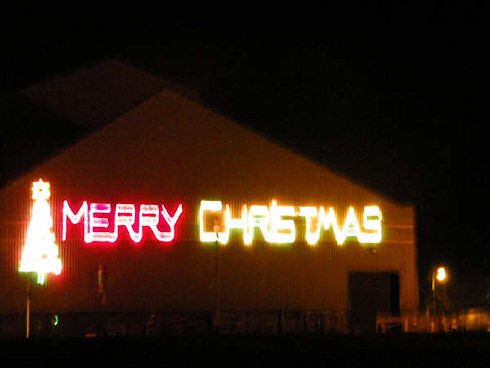 Picture of the words 'Merry Christmas' in neon lighting on the side of a warehouse