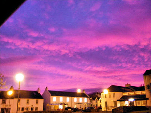 Picture of a colourful morning sky over the main road of a small village