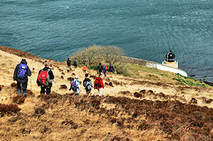 Picture of walkers approaching a lighthouse, the sea below