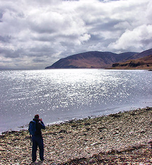 Picture of a man taking a picture of the scenery on the shore of a sound between two islands