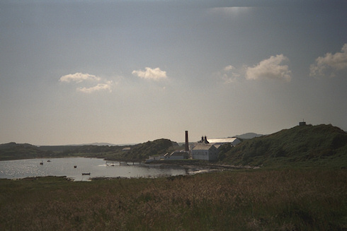 Picture of a whisky distillery (Lagavulin) at a sunny bay on a beautiful sunny day