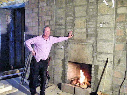Picture of a man standing in front of a future fireplace in an under construction hotel