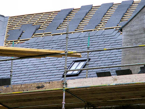 Picture of the under construction roof of a building with the slates going up
