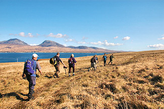 Picture of walkers walking along the Sound of Islay with the Paps of Jura in the background
