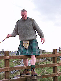 Picture of a walker in kilt climbing over a stile