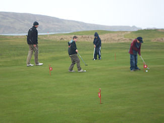 Picture of a group of children practising golf putts under the watchful eyes of a coach
