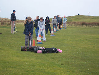 Picture of a group of children practising golf swings under the watchful eyes of a coach