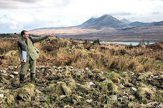 Picture of a head gamekeeper pointing into the distance, some distinctively shaped mountains in the background