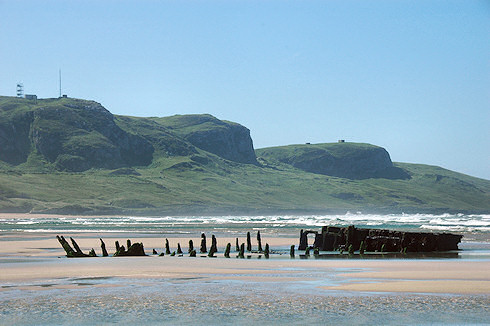 Picture of a wreck on a beach, high cliffs in the background, all under a brilliant blue sky