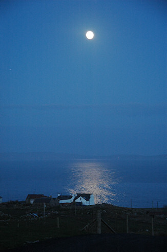 Picture of the moon shining above a small coastal hamlet