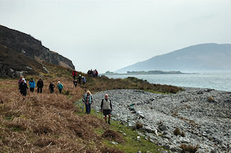 Picture of walkers on the shore of a sound between two islands