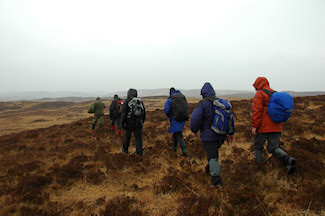 Picture of a group of walkers on a rainy moorland stretch