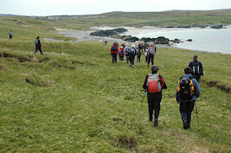 Picture of a group of walkers approaching a bay with a farm