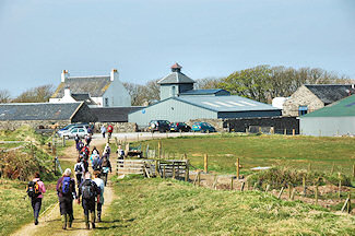 Picture of walkers approaching a farm distillery