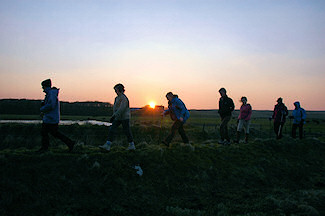 Picture of some walkers on a sea wall with the sun setting in the background