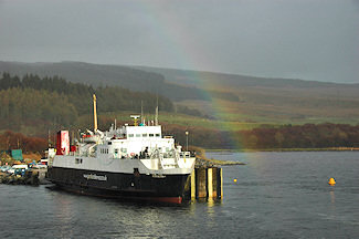 Picture of a old ferry under a partial rainbow