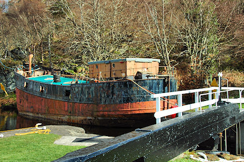 Picture of an old puffer moored next to a lock