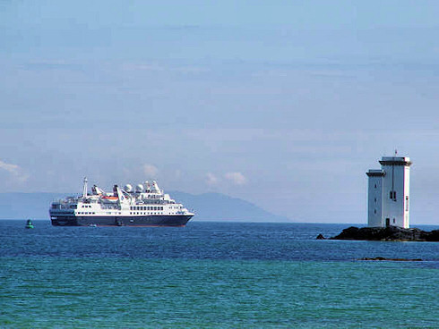 Picture of a black cruise liner anchored near a lighthouse