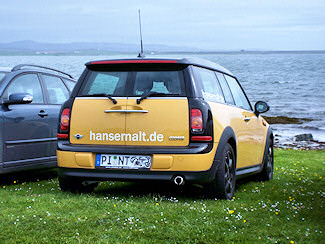 Picture of the back of a yellow Mini Clubman with the lettering hansemalt.de