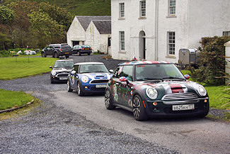 Picture of three Mini Cooper cars in a row in front of a house