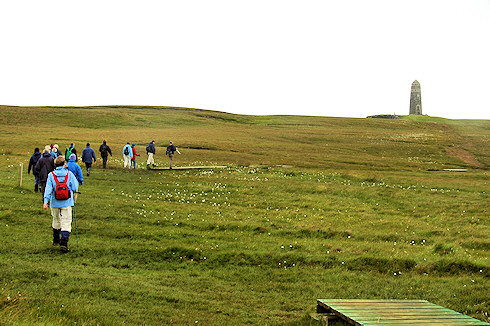 Picture of a group of walkers on slightly hilly ground, a monument in the distance