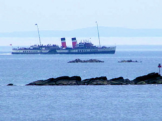 Picture of a paddle steamer cruising along a rocky shore line