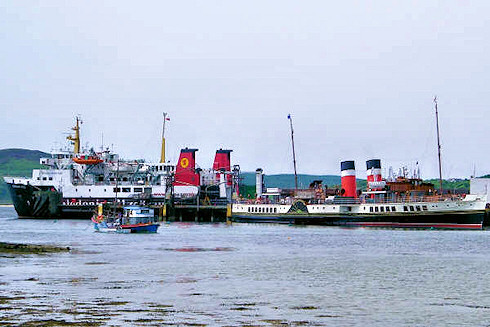 Picture of a paddle steamer at a small pier, a modern car ferry in the background