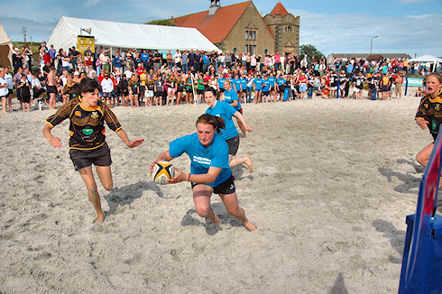 Picture of a player about to score a try in a beach rugby game
