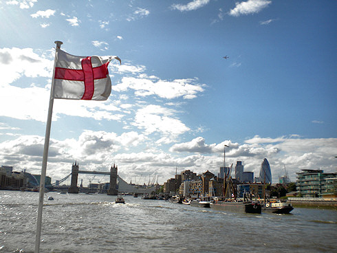 Picture of Tower Bridge in London seen from a river cruise ship, the England flag flying on the bow