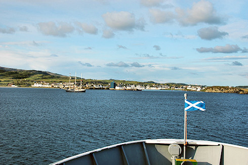 Picture of the view from a ferry arriving in a small island port, the Scottish Flag (Saltire) flying on the bow
