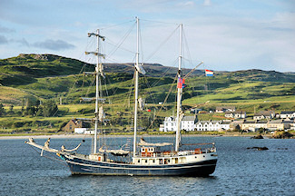 Picture of a tall ship anchored outside a small coastal village