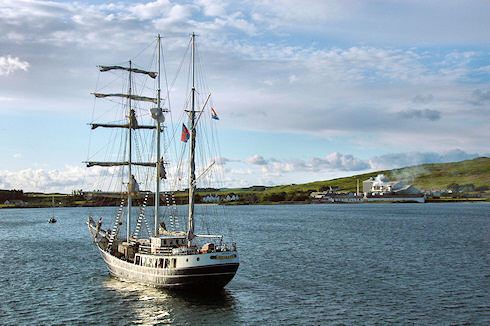 Picture of the tall ship Thalassa anchored in a bay with industrial maltings and a disused distillery in the background