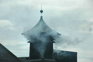 Picture of a pagoda at a whisky distillery with peat smoke billowing out