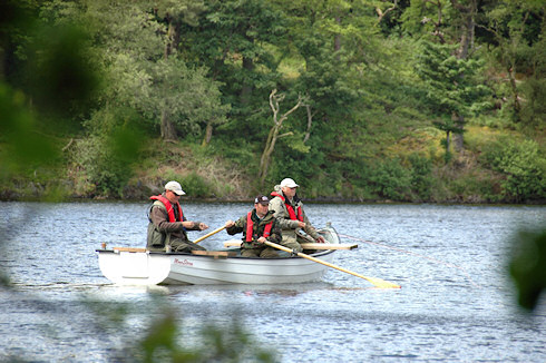 Picture of a boat with a rower and two men fly fishing