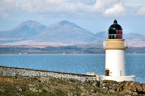 Picture of a small lighthouse with some distinctly shaped mountains in the background