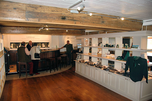 Picture of the Laphroaig distillery visitor centre, people at a bar and some shop shelves with merchandise