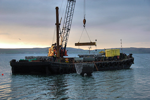 Picture of a barge crane lowering a 'special mattress' for a waterworks outlet into the water