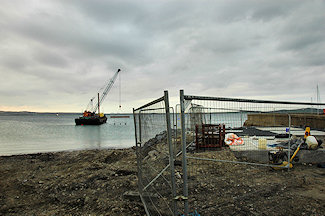 Picture of a construction fence around a water treatment outlet, a barge with a crane in the background