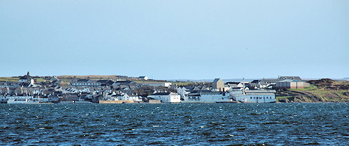 Picture of a coastal village (Bowmore on Islay) seen across a sea loch. Bowmore distillery clearly visible