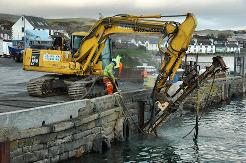 Picture of a digger with a drill attached working on a quay wall