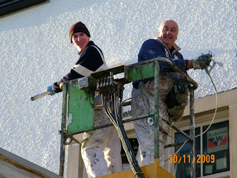 Picture of two painters in a cherry picker