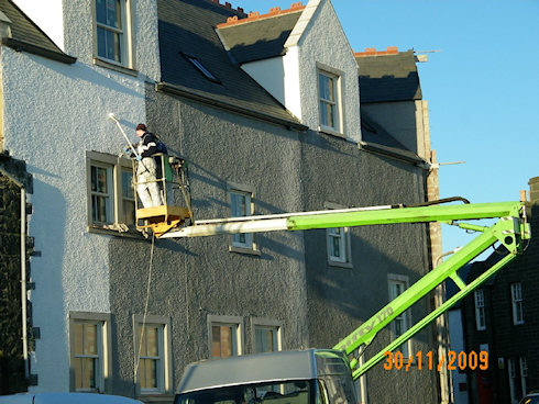 Picture of two painters at work on a cherry picker