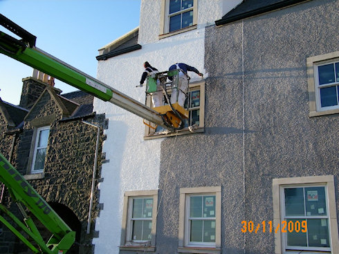 Another picture of two painters at work on a cherry picker