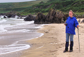 Picture of a woman in a blue jacket on a sandy beach
