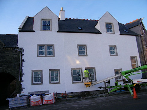 Picture of a hotel being painted white, this side of the building almost finished