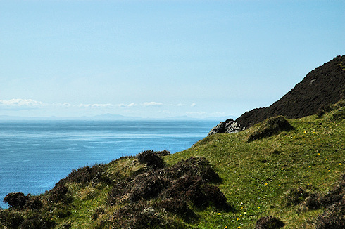 Picture of a view over a heather clad cliff face with land on the other side of a sea strait
