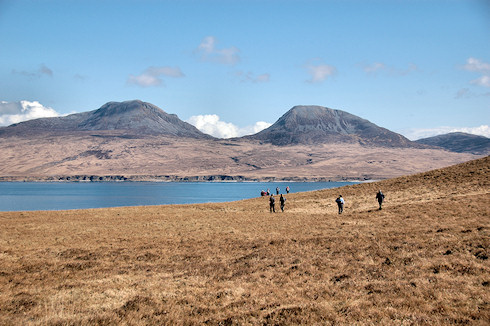 Picture of walkers approaching a sound between two islands, two round shaped hills on the other island