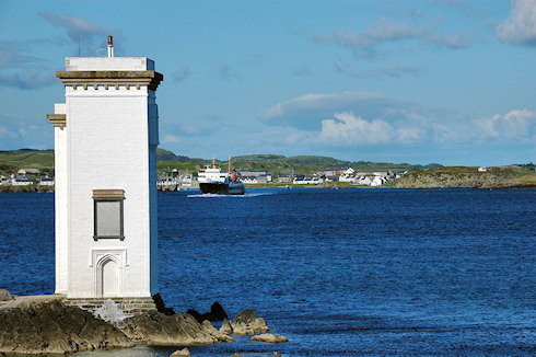 Picture of a ferry leaving a small port, seen from behind a lighthouse