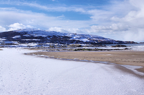 Picture of a beach covered in snow, behind it a hillside in snow