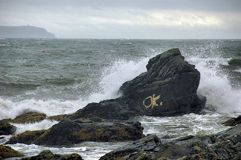 Picture of waves breaking over a rock with the letters 'ok' painted on it